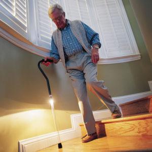 Hombre mayor andando con bastón con luz