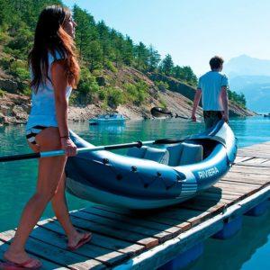 Dos chicos llevando un kayak hinchable
